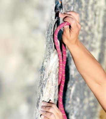 Detall de les mans d'un escalador pujant una montanya
