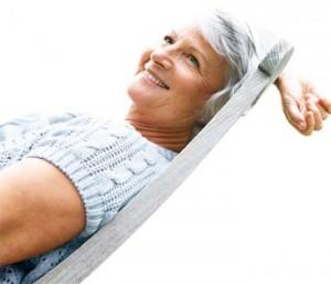 Señora mayor descansa feliz en una hamaca.