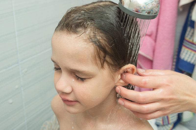 madre lava la oreja a niña en la ducha